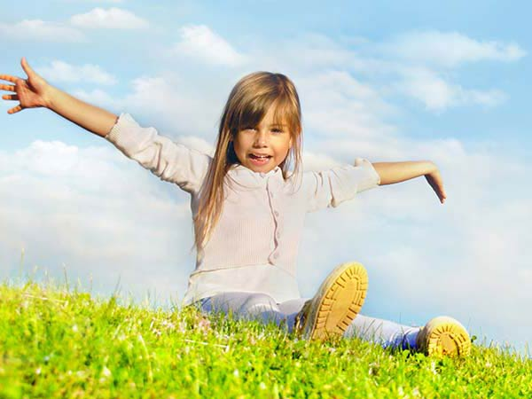Kind mit offenen Armen auf einer Wiese